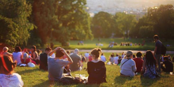 Young people sitting in a park at sundown