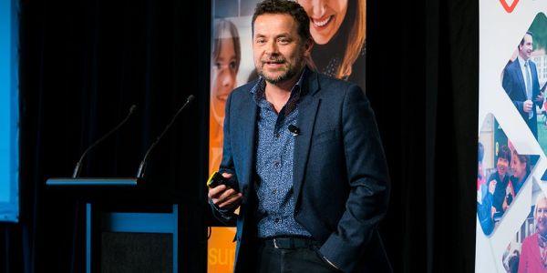 Christian van Nieuwerburgh presenting on a stage